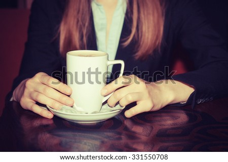 Coffee break. Close up portrait of female hands holding cups of hot beverage cappuccino latte mocha on rustic wooden table isolated on dark red background in fancy coffee shop, cafe. relaxation moment - stock photo