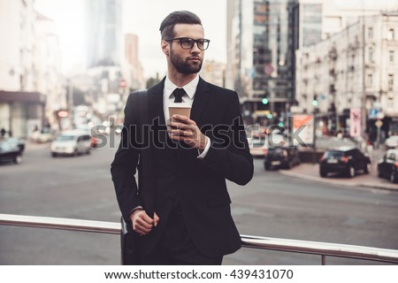 Coffee break. Confident young man in full suit holding coffee cup and looking away while standing outdoors with cityscape in the background  - stock photo