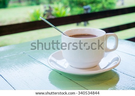 Coffee break for refreshment. Ceramic cup of coffee on green wooden table. - stock photo