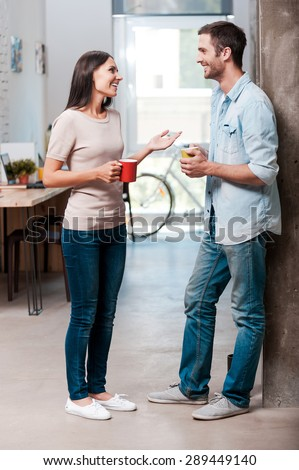Coffee break. Full length of two cheerful young people talking and smiling during a coffee break in office  - stock photo