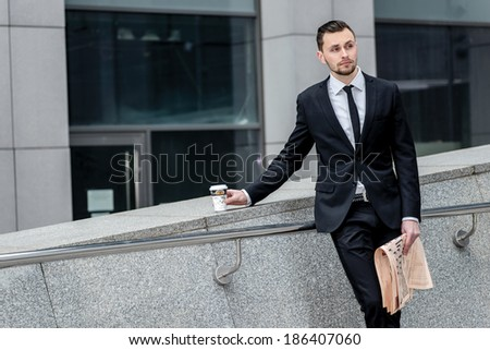 Coffee break. Handsome successful businessman holding a cup of coffee and the newspaper at the same time looking forward.