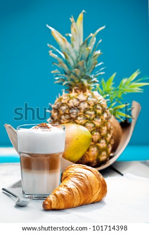 Coffee Break on a deck at the beach with a croissant and tropical fruits as a breakfast. - stock photo