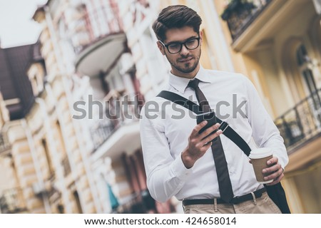 Coffee break on a go. Low angle view of confident young man in glasses holding coffee cup and using his smart phone while walking outdoors - stock photo