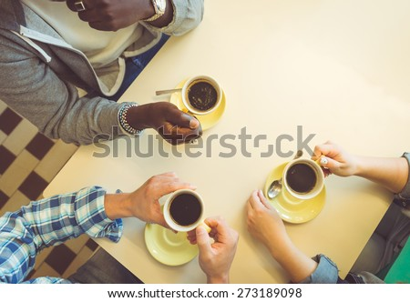 coffee break. three friends sitting and having a coffee in a store. concept about people, coffee, and bars - stock photo