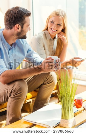 Coffee break with colleague. Smiling young woman holding mobile phone while young man holding cup of coffee and sitting near her in the rest area of the office - stock photo