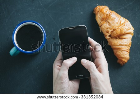 coffee break with Croissant while using mobile phone - stock photo