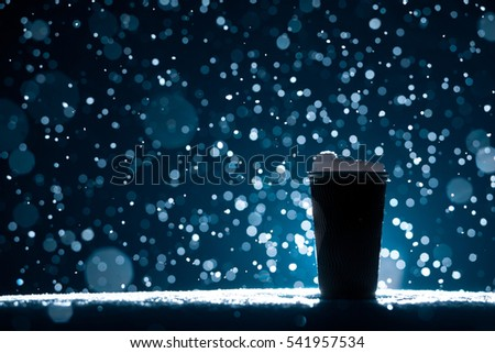 coffee break with hot drink in snowy weather; paper cup with tea on snow background;