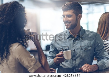 Coffee break with joy. Young handsome man holding coffee cup and discussing something with young woman while standing at bar counter - stock photo