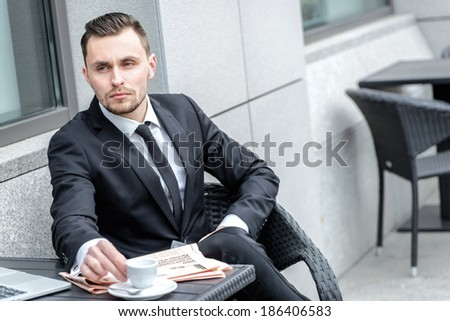 Coffee break. Young businessman holding a cup of coffee in hand and looking forward.