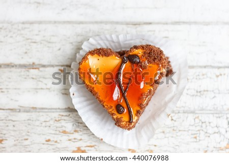 Coffee cake in the shape of a heart on a white wooden background - stock photo