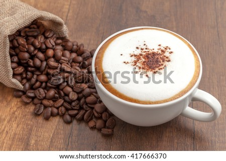 Coffee cappuccino and coffee beans on wooden background - stock photo