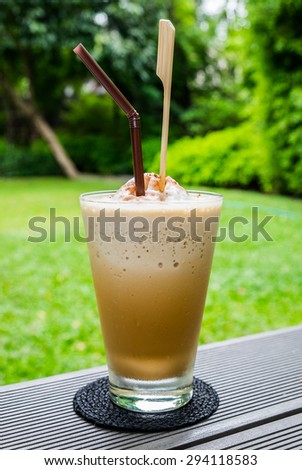 Coffee cappuccino churn froth in glass and straw on green garden