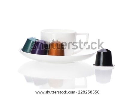 coffee capsules and cup isolated on white background - stock photo