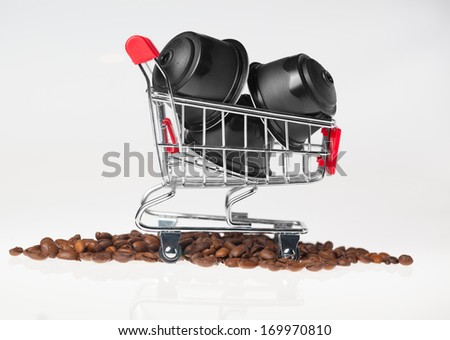 Coffee capsules in a small shopping cart in coffee grains on white background.