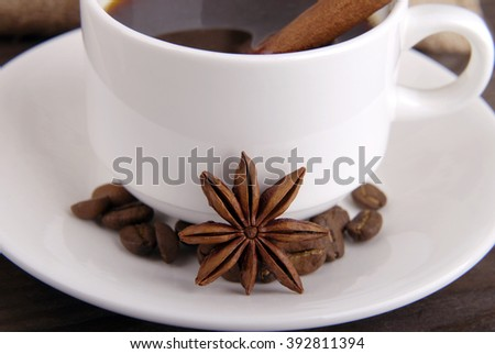 Coffee composition. White cup with black coffee on white saucer. Anise, cinnamon stick and coffee beans as coffee decor. - stock photo