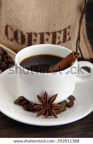 Coffee composition. White cup with black coffee on white saucer. Coffee bag. Scoop with coffee beans. Anise, cinnamon stick and coffee beans as coffee decor. - stock photo