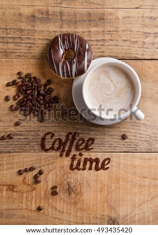 Coffee composition with cup and donut on wooden background, selective focus