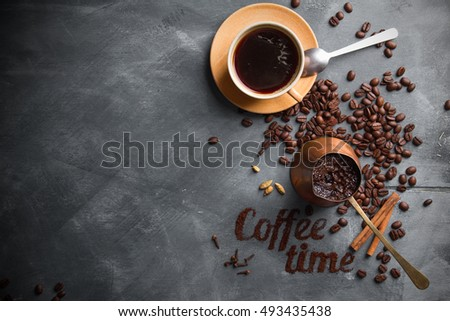 Coffee composition with cup and old coffee pot on dark background, selective focus