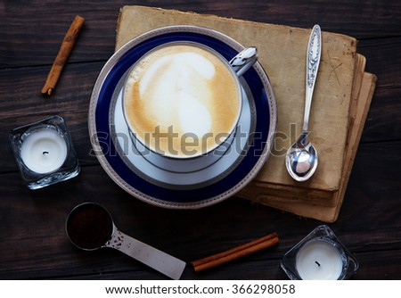 Coffee composition with old book, white tea candles, silver spoon, ground coffee and cinnamon on dark wooden background. - stock photo