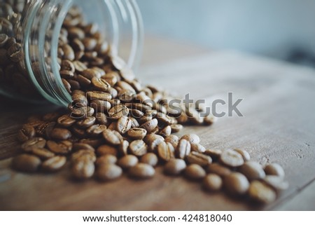 coffee concept : coffee beans in the coffee bottle  soft focus to coffee beans , in coffee shop cafe vintage color tone , for poster coffee or advertising coffee for coffee shop - stock photo