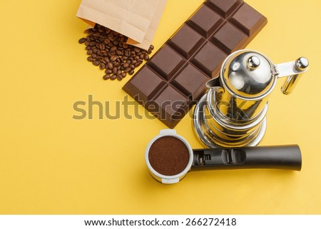 Coffee concept. Coffee in a holder, coffee-beans, bar of chocolate, coffee-pot on yellow background - stock photo