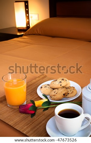 Coffee, cookies, orange juice and a pair of roses over the bed for a romantic breakfast in an orange predominant image. - stock photo