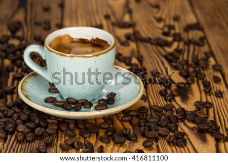 Coffee culture. Cup of coffee on a saucer filled with roasted aromatic coffee beans. - stock photo