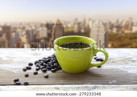 Coffee cup above blurred cityscape - stock photo