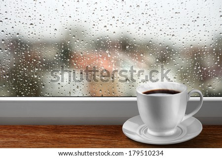 Coffee cup against window with rainy day view - stock photo