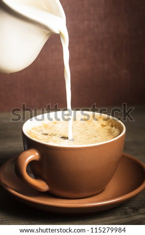Coffee cup  and a pouring milk - stock photo