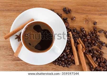 Coffee cup and beans, cinnamon sticks, anise on wooden table, brown background - stock photo