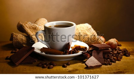 coffee cup and beans, cinnamon sticks, nuts and chocolate on wooden table on brown background