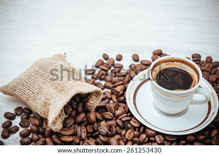 Coffee cup and beans on a biege burlap background. roasted coffee beans