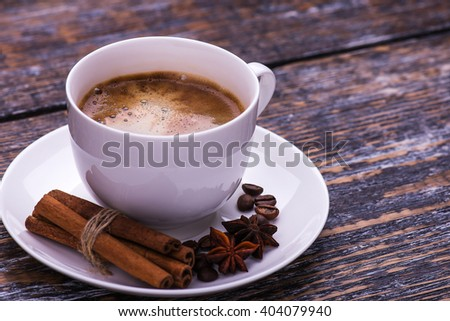 Coffee cup and beans on a wooden table. Dark background. - stock photo