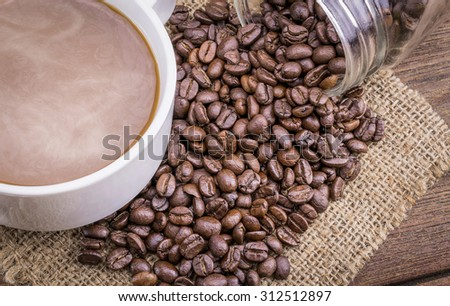 Coffee cup and beans on a wooden table, Dark background Vintage style.