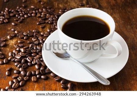 Coffee cup and beans on old wooden table  - stock photo