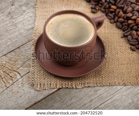 Coffee cup and beans on wooden table background