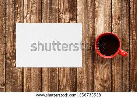 Coffee cup and blank paper on wooden table - stock photo