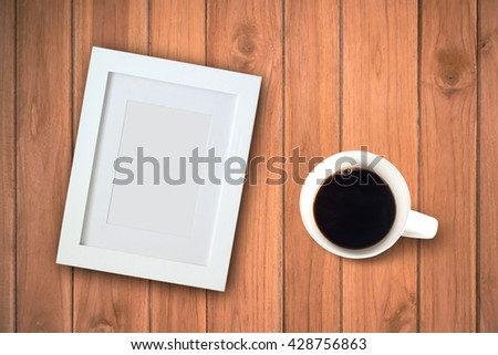 Coffee cup and blank photo frame on wooden table background