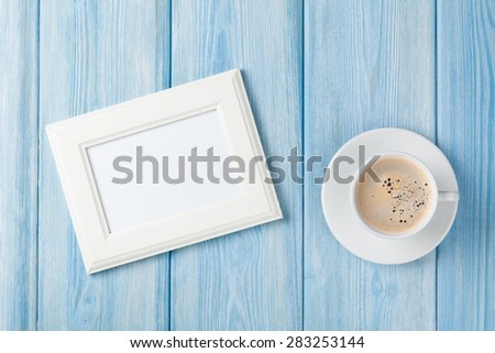 Coffee cup and blank photo frame on wooden table background. Top view with copy space