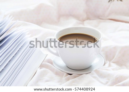 Coffee cup and book in bed, cozy relaxing morning coffee