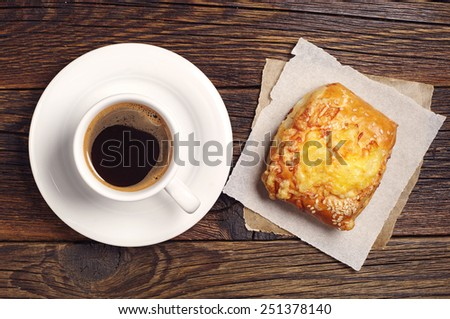 Coffee cup and bun with cheese on dark wooden table, top view - stock photo
