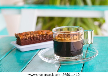 Coffee cup and cake on white blue table - stock photo