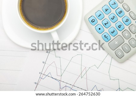 Coffee cup and calculator over stock charts - view from top - stock photo