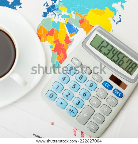 Coffee cup and calculator over world map - view from top - 1 to 1 ratio - stock photo