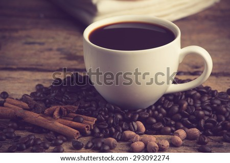 Coffee cup and coffee bean on a wooden table. Dark background vintage color
