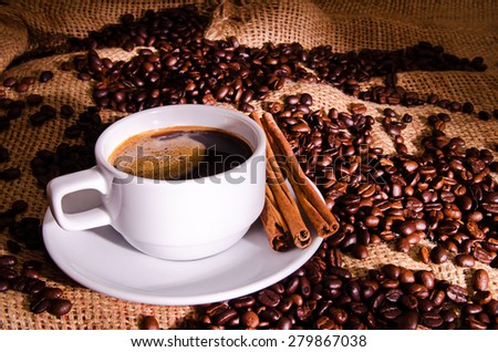 Coffee cup and coffee beans around  - stock photo
