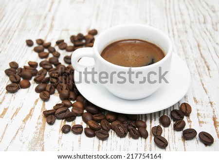 Coffee cup and coffee beans on a wooden background - stock photo