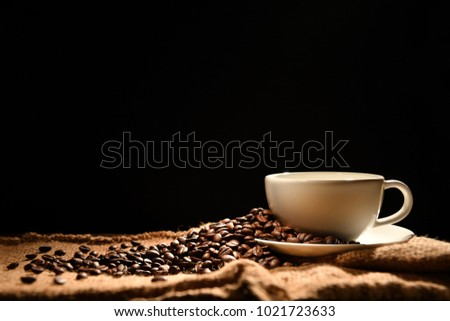 Coffee cup and coffee beans on black background