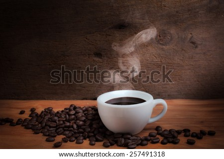Coffee cup and coffee beans on old wooden background with stream